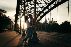 Romantic portrait of the happy couple in love. They are tenderly hugging and leaning on the iron archway during the. Sunset. Wroclaw. Poland location Royalty Free Stock Photos