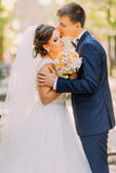 The romantic portrait of the happy newlyweds. The groom is kissing the bride on the head in the park. The romantic portrait of the happy newlyweds. The groom is Stock Photography