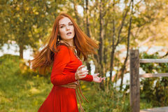 Romantic portrait of the woman in airy red dress dancing on the bridge Stock Photography