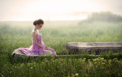 Romantic portrait of woman in ruins. Romantic portrait of young woman in airy pink dress sitting in ruins at sunrise Royalty Free Stock Photography