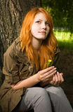 Romantic portrait of a young redhead. Romantic portrait of a young redhead girl sitting outdoors in the park stock image