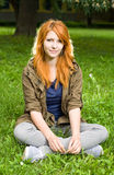 Romantic portrait of a young redhead. Romantic portrait of a young redhead girl sitting outdoors in the park stock photography