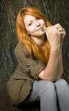 Romantic portrait of a young redhead girl. Romantic portrait of a young redhead girl sitting outdoors in the park royalty free stock photo