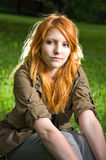 Romantic portrait of a young redhead girl. Romantic portrait of a young redhead girl sitting outdoors in the park stock photography