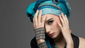 Romantic portrait of young woman in a turquoise turban with jewe Stock Photos
