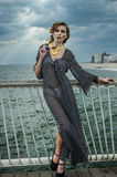 Romantic portrait of young woman wearing black and white dress on the pier. Stock Photo