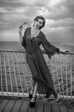 Romantic portrait of young woman wearing black and white dress posing on the pier. royalty free stock photography