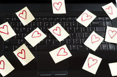 Romantic post it notes. Post it notes with harts  scatered over  keyboard Royalty Free Stock Images