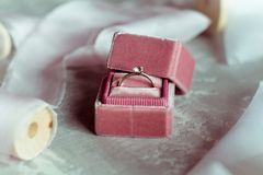 Romantic present: pink velvet box with a wedding ring and light satin ribbons on a gray background. Selective focus. Close up. Top view. vintage photo royalty free stock photos