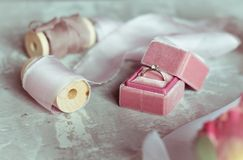 Romantic present: pink velvet box with a wedding ring and light satin ribbons on a gray background. Selective focus. Close up. Top view. vintage photo royalty free stock photo