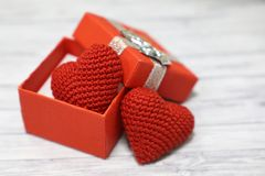 Valentine gift box with red knitted hearts on light wooden table royalty free stock photos