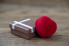 Romantic presents in honor of Valentine`s day, red heart and case. royalty free stock image