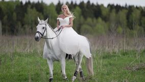 romantic princess in white wedding dress is riding horse on field, fairytale and fantasy