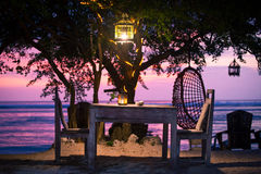 A romantic private beach dinner with candles at sunset. With beautiful evening light under a tree with a lantern Royalty Free Stock Images