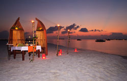 Romantic private dinner at the resort. Table served for romantic dinner on the beach, beautiful colorful sunset on the background Stock Photo