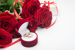 Romantic red roses with wedding rings. Valentine day background Stock Photos