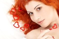 Romantic redhead with read hea. Portrait of romantic redhead with read hearts royalty free stock photos