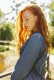 Romantic redhead young woman in denim shirt posing in rays of s. Romantic redhead young model in denim shirt posing in rays of sun at the forest royalty free stock photography
