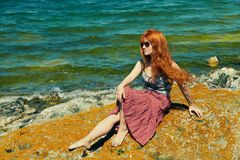 Romantic redhead woman in a dress on sea coast. girl in the summer outdoors royalty free stock photos
