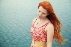 Romantic redhead young woman in a dress on sea coast. Girl in the summer outdoors royalty free stock images