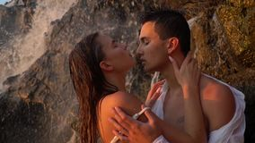 Romantic relations under the waterfall, slow motion. Wet guy and girl stand under a waterfall among the rocks and enjoy the closeness to each other, slow motion stock video