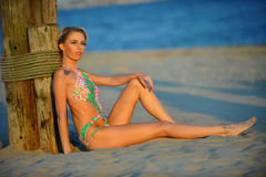 Romantic relaxed woman in swimsuit sitting on the sand Stock Photo