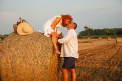 Romantic date on a freshly cut field near a haystack Royalty Free Stock Photography