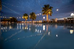 Romantic restaurant by the pool at night. Reflection in water royalty free stock photography