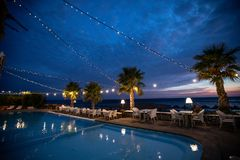 Romantic restaurant by the pool at night. Reflection in water royalty free stock image