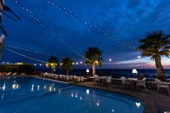 Romantic restaurant by the pool at night. Reflection in water royalty free stock photo