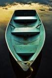 Romantic rowboat. Blue rowboat on lake shore during the sunset stock photography