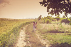 Romantic rural path. Girls walking in romantic colorful rural path among fields Stock Photography