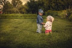 Romantic scene with couple of children boy and girl holding with hands at sunset in rural field symbolizing love and togetherness. Pathetic romantic scene with Royalty Free Stock Images