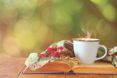 Romantic scene of cup of coffee next to old book in front of countryside bokeh landscape background. Romantic scene of cup of coffee next to old book in front royalty free stock image