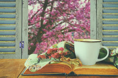 Romantic scene of cup of coffee next to old book in front of countryside view outside of the old rustic window Royalty Free Stock Image