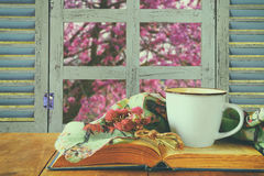 Romantic scene of cup of coffee next to old book in front of countryside view outside of the old rustic window Royalty Free Stock Photo
