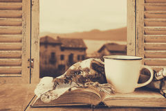 Romantic scene of cup of coffee next to old book in front of countryside view outside of the old rustic window Stock Images