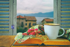 Romantic scene of cup of coffee next to old book in front of countryside view outside of the old rustic window Stock Photography