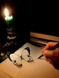 Romantic scene with hand of woman writing. Hand of woman writing on a book with candle and paper butterfly Royalty Free Stock Image