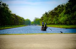 Rowing a boat a cross blue river stock photography