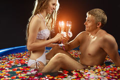 Romantic scene in pool. Young couple relaxing with champagne in pool  with rose petals Royalty Free Stock Photo