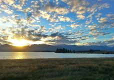 Romantic scenery. With grassfield, lake, mountains and lovely blue sky before sunset Royalty Free Stock Images