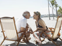 Romantic Senior Couple On Deckchairs At Beach Royalty Free Stock Photography