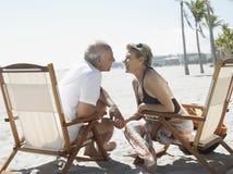Romantic Senior Couple On Deckchairs At Beach Royalty Free Stock Photography