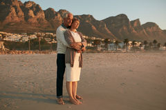 Romantic senior couple embracing on the sea shore Stock Photos