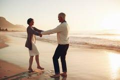 Romantic senior couple enjoying a day at the beach Stock Photos