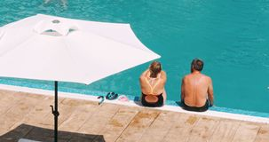 Romantic senior couple with the feet in the pool. stock video footage