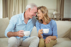 Romantic senior couple having cup of coffee in living room Stock Photo