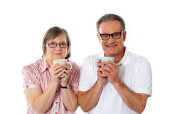 Romantic senior couple holding coffee mugs Stock Images