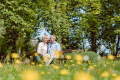 Romantic senior couple in love dating outdoors in an idyllic par Stock Photos
